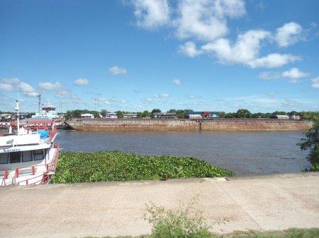 Barco e chata subindo o rio. Ao fundo, casas da Isla Margarita.